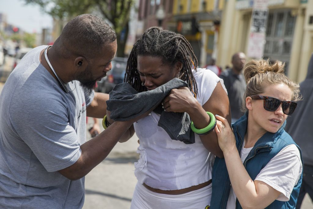 Shameeka Dream, of Baltimore, Md. is helped after being sprayed in the eyes with a crowd dispersement during a demonstration after an evening of riots following the funeral of Freddie Gray on Tuesday, April 28, 2015, in Baltimore. (photo credit: AP Photo/Evan Vucci)