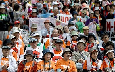 People, including survivors of the nuclear bombings in Japan in 1945, front, participate in an anti-nuclear rally in Union Square in New York, Sunday, April 26, 2015. (AP Photo/Seth Wenig)