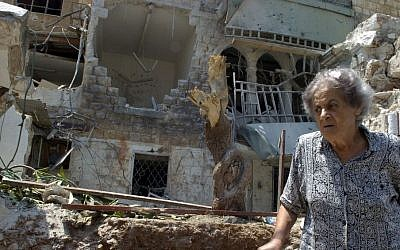 An Israeli woman walks in front of a building destroyed by a Katyusha rocket in the town of Haifa on August Monday 07.2006. (photo credit: Max Yelinson /Flash90)