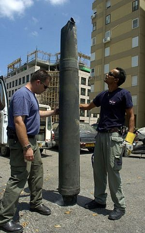 Israeli explosives experts inspect a Hezbollah rocket after it landed in the northern Israeli city of Haifa August 9, 2006. (photo credit: Max Yelinson /Flash90)