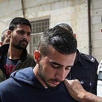 Niv Asraf (C) and his friend Eran Negauker (L), 22-year-olds from Beersheba, are seen at the Jerusalem Magistrate's Court for remand extension on April 3, 2015, a morning after Asraf was found in Kiryat Arba after being falsely reported as missing (Hadas Parush/ Flash90)
