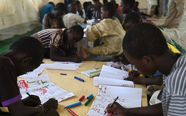 Young Nigerian refugees draw on April 6, 2015 during a therapy program managed by UNICEF in a refugee camp near Baga Sola (photo creidt: AFP /PHILIPPE DESMAZES)