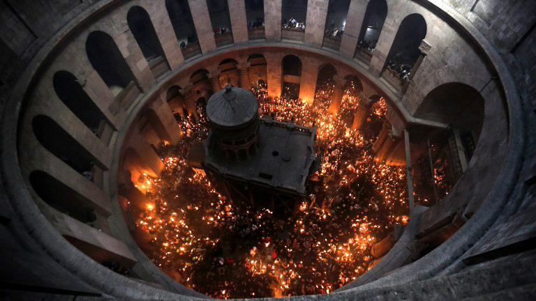 """File: Christian Orthodox worshipers hold up candles lit from the """"Holy Fire"""" as thousands gather in the Church of the Holy Sepulcher in Jerusalem's Old City, on April 11, 2015. (photo credit: AFP/Ahmad Gharabli)"""