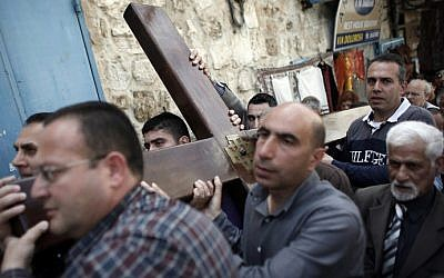 Catholic worshipers carry a wooden cross during the Good Friday procession along the Via Dolorosa (Way of Suffering) on April 3, 2015 in Jerusalem's Old City (photo credit: AFP/Thomas Coex)