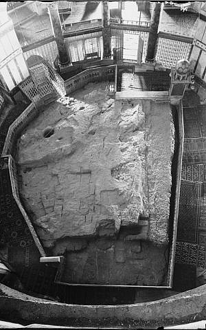 The Foundation Stone in the floor of the Dome of the Rock shrine in Jerusalem. The round hole at upper left penetrates to a small cave, known as the Well of Souls, below. The cage-like structure just beyond the hole covers the stairway entrance to the cave. (Photo credit: Wikipedia)