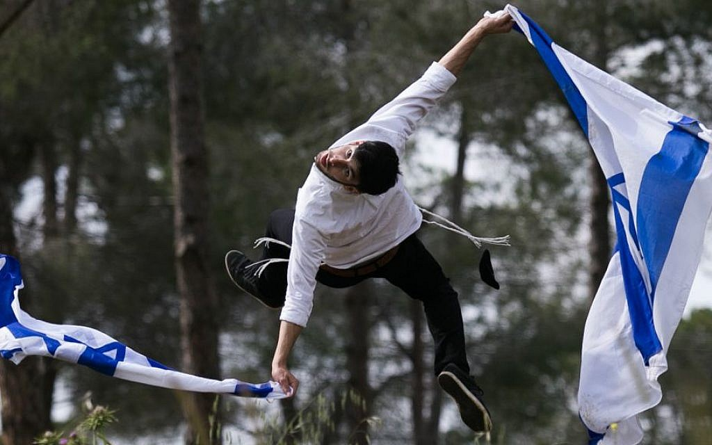 Ultra-Orthodox Jewish Mickey Hayat practices Capoeira, a Brazilian martial art, as he holds an Israeli national flag, ahead of Israeli Independence Day, on April 17, 2015. (Nati Shohat/Flash 90)