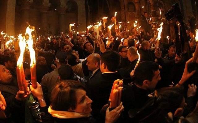 """Christian Orthodox worshipers light candles from the """"Holy Fire"""" as thousands gather in the Church of the Holy Sepulcher, traditionally believed to be built on the site where Jesus was crucified, buried and resurrected, in Jerusalem's Old City, on April 11, 2015. (photo credit: AFP/Thomas Coex)"""