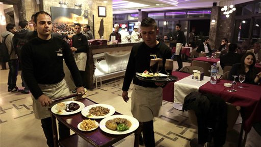 """In this Thursday, April 16, 2015 photo, Palestinian waiters work at at the rooftop restaurant """"Level Up,"""" in Gaza City (photo credit: AP/Khalil Hamra)"""
