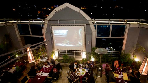"""In this Thursday, April 16, 2015 photo, Palestinians spend the evening at the rooftop restaurant """"Level Up,"""" in Gaza City (photo credit: AP/Khalil Hamra)"""