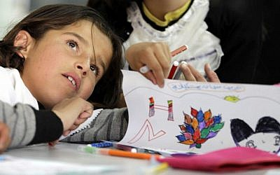 """A child draws during the inauguration of the """"Ideas Box"""" kit, an initiative of French NGO Libraries without Borders (BSF), at Azraq refugee camp hosting Syrian refugees who fled the deadly conflict in their country on April 28, 2015 in Jordan, some 60 miles (100 kilometers) east of Amman. Four multicolored cubes and two storage units make up the BSF-designed kit library dubbed an """"Ideas Box."""" (Photo credit: AFP photo/Khalil Mazraawi)"""