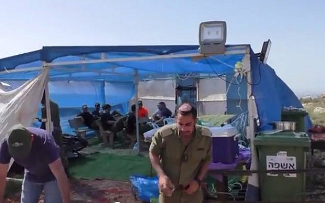 Still from a video showing IDF soldiers enjoying music and barbecuing at a tent established upon the ruins of an illegal outpost near the West Bank city of Hebron (photo credit: YouTube screen cap/Rabbis for Human Rights)