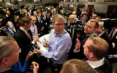 Former Florida gov. Jeb Bush (center), mingles at a 'Politics and Eggs' event, a breakfast fixture for 2016 presidential prospects, at Saint Anselm College in Manchester, NH, Friday, April 17, 2015. (photo credit: AP/Elise Amendola)