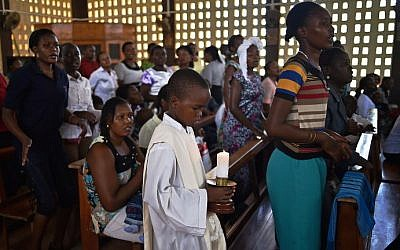A young altar server holds a candle during a Easter service at the Catholic cathedral in Garissa on April 5, 2015, mourning the country's worst ever massacres, the killing of almost 150 people in an attack on a university by Somalia's Shabab Islamists that occurred on April 2 at Garissa's University. (photo credit: AFP/Carl De Souza)