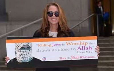 """American Freedom Defense Initiative head Pamela Geller, holding a political advertisement containing the phrase """"Hamas Killing Jews"""" (screen capture: YouTube)"""