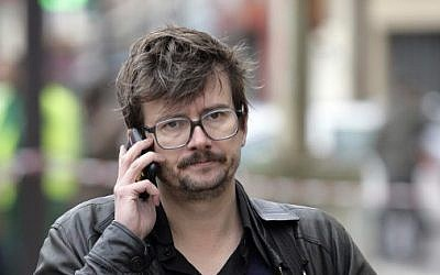 A file photo taken on November 2, 2011 shows French satirical newspaper Charlie Hebdo's cartoonist Luz using his cell phone in front of the offices of the paper in Paris (photo credit: AFP/ ALEXANDER KLEIN)