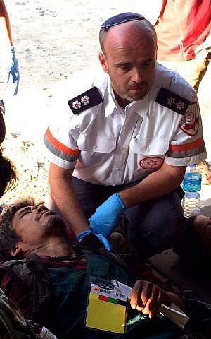 Ilan Klein, a paramedic with MDA, treat local residents injured in the Nepal earthquake on Sunday in Kathmandu. (photo courtesy: MDA)