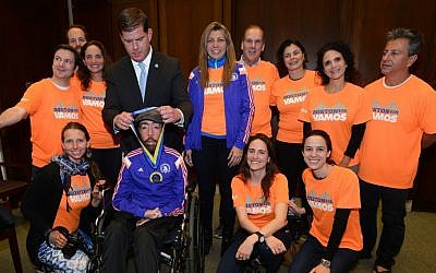 Maickel Melamed, in a wheelchair and flanked by his support team, receives a medal from Boston Mayor Martin Walsh, April 21, 2015. (Photo Credit: JTA/City of Boston, Mayor's Office)