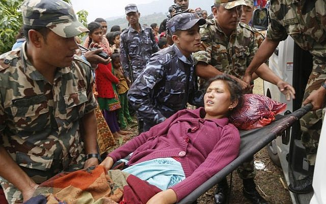 Sita Karka, suffering two broken legs from Saturday's massive earthquake, is assisted into an ambulance by Nepalese soldiers and police after arriving by helicopter from the heavily-damaged Ranachour village at a landing zone in the town of Gorkha, Nepal, Tuesday, April 28, 2015. (Photo credit: AP/Wally Santana)