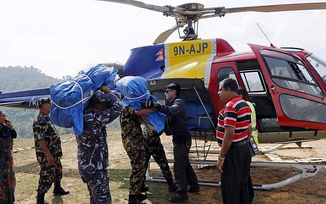 A helicopter is loaded with supplies at a relief staging area of landing zone near Saturday's massive earthquake's epicenter in the town of Gorkha, Nepal, Tuesday, April 28, 2015. (Photo credit: AP/Wally Santana)