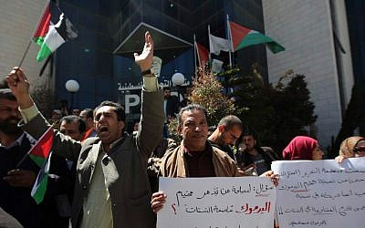 Palestinians shout slogans as they hold banners during a gathering in solidarity with the Palestinians living in Syria's Yarmouk camp, on April 5, 2015 outside Palestinian Liberation Organization (PLO) headquarters in Ramallah, the West Bank (photo credit: AFP/ ABBAS MOMANI)