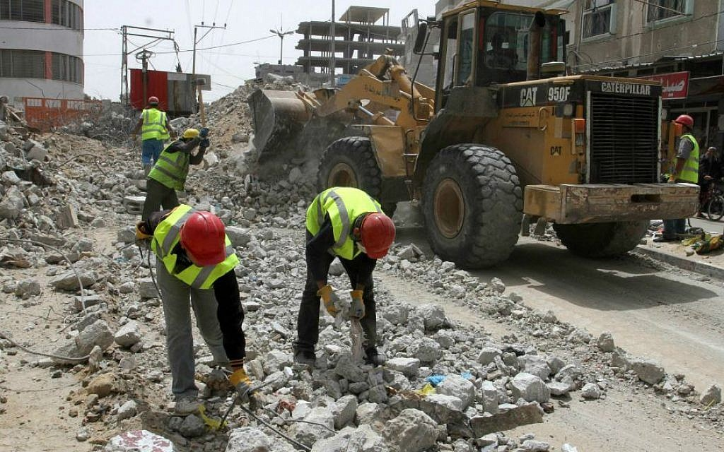 Palestinian workers rebuild the commercial center, destroyed by Israeli shelling during Operation Protective Edge, in Rafah in the southern Gaza Strip, on April 20, 2015. The reconstruction is funded by the United Nations Development Program (UNDP). (Abed Rahim Khatib/Flash 90)