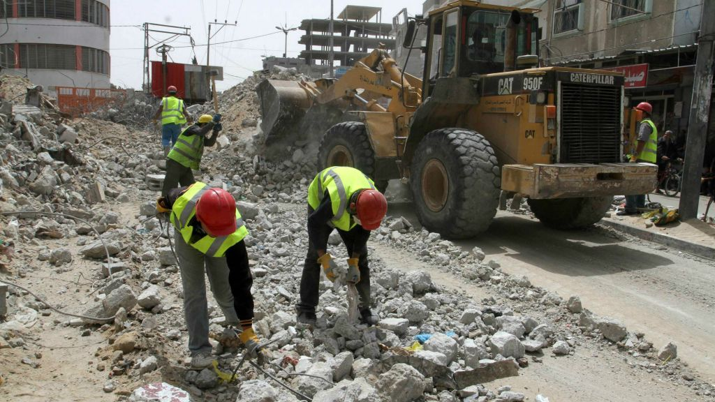 Palestinian workers rebuild the commercial center, destroyed by Israeli shelling during Operation Protective Edge, in Rafiah in the southern Gaza Strip, on April 20, 2015. The reconstruction is funded by the United Nations Development Program (UNDP). (Abed Rahim Khatib/Flash 90)