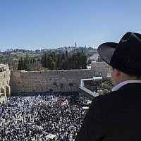A young man looks down at the thousands gathered at the Western Wall for the annual priestly blessing April 6, 2015. (Photo credit: Yonatan Sindel/Flash90)