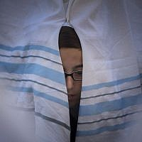 A boy peeks out from behind a prayer shawl during the annual priestly blessing at the Western Wall April 6, 2015. (Photo credit: Yonatan Sindel/Flash90)
