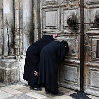 Christian Orthodox priests look through a hole in the main door of the Church of the Holy Sepulcher, before the Holy Fire ceremony around Jesus's tomb, in Jerusalem's Old City, on April 11, 2015. (AFP/Thomas Coex)