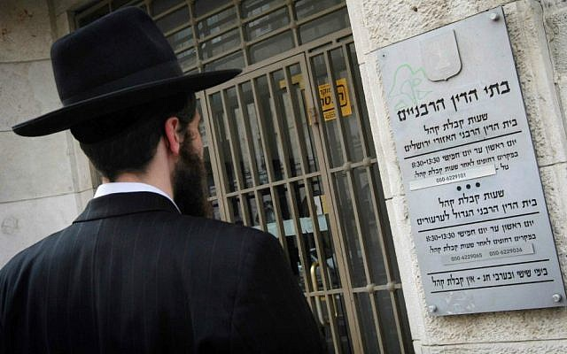 Illustrative: A man stands outside the Jerusalem Rabbinical Court. (Miriam Alster/Flash90)