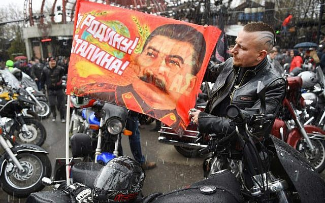 Illustrative: A Russian biker shows a banner depicting Joseph Stalin and reading a WWII slogan 'For the Motherland! For Stalin!' in Moscow on April 25, 2015. (photo credit: AFP/Dmitry Serebrayakov)