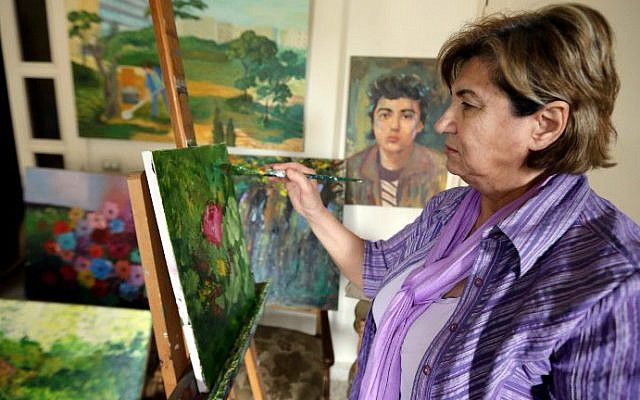 Mariam Saidi paints as she stands in front of an oil painting of her son Maher (center-background), who disappeared in 1982 at the age of 15 while fighting near Beirut, at her house in the Lebanese capital on April 8, 2015. (photo credit: AFP/Joseph Eid)
