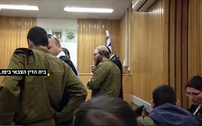 Israel Defense Forces soldier Elad Yaakov Sela (center), 25, in court on April 13, 2015 (screen capture: Walla news)