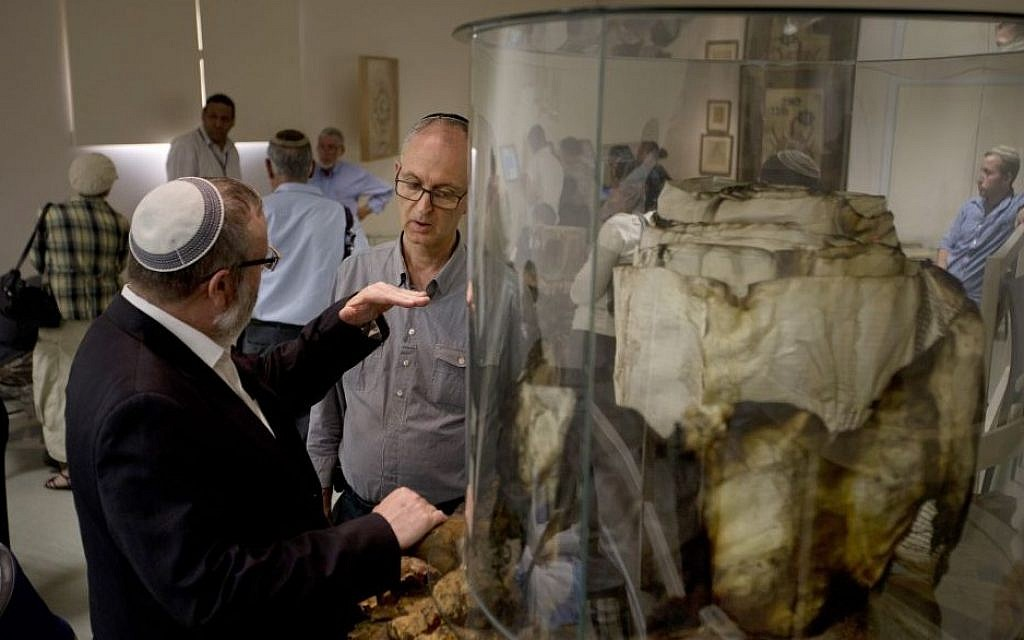 In this Monday, April 6, 2015, photo, David Hershkoviz listens to Avraham Krieger, the institute director of the Shem Olam Holocaust, as he speaks about the Torah scroll from the Warsaw ghetto in Kfar Haroeh, Israel. (Photo credit: AP/Ariel Schalit)
