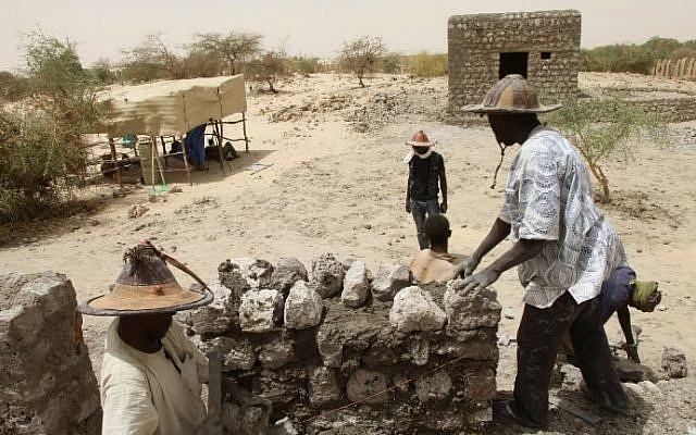 People work on the reconstruction of the mausoleums in the Three Saints cemetery on April 8, 2015 in Timbuktu, northern Mali. (Photo credit: AFP/SEBASTIEN RIEUSSEC)