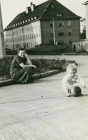 Dina Lichtman playing at the Bergen-Belsen DP camp as her mother Bella Cypris looks on, 1949. (photo credit: courtesy of Dina Lichtman)