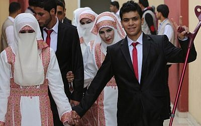 Palestinian bride Marwa Mousa and her groom Ahmed Abu Salama take part in a mass wedding ceremony in Gaza City, on April 11, 2015. Nearly 200 Palestinian couples were married in a ceremony funded by an Emirati governmental organization. Photo credit: AFP/ MAHMUD HAMS)