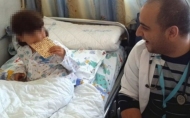 A Syrian boy hospitalized in Israel has his first taste of matzah on Tuesday, April 7, 2015 (courtesy Ziv Hospital)