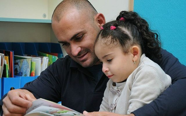 Father reads to his daughter in Baqa al-Gharbiyye. (photo credit: Akmal Nagnagy)