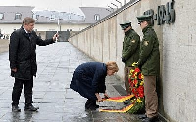 German Chancellor Angela Merkel lays a wreath at the International Memorial of former Nazi concentration camp of Dachau, southwestern Germany, during a ceremony to mark 70 years since it was liberated by US forces on May 3, 2015. American army trucks rolled into Dachau, northwest of Munich, on April 29, 1945 to discover the unspeakable horror that had led to more than 41,000 people being killed, having starved or died of disease. (photo credit: AFP PHOTO / CHRISTOF STACHE)