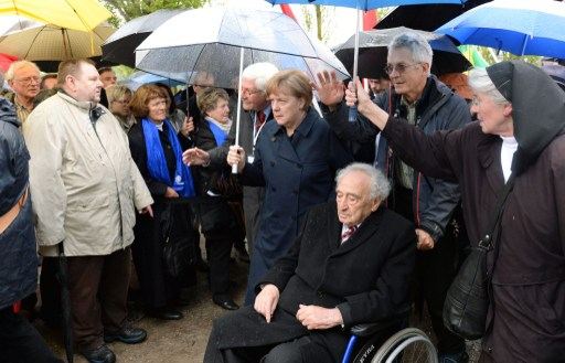German Chancellor Angela Merkel (C) walks with Holocaust survivor Max Mannheimer (3th R) at former Nazi concentration camp of Dachau, southwestern Germany, during a ceremony to mark 70 years since it was liberated by US forces on May 3, 2015. (photo credit: AFP PHOTO / CHRISTOF STACHE)