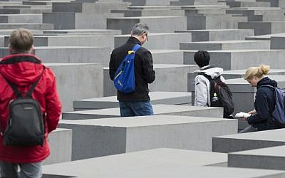 Tourists visit the Memorial to the Murdered Jews of Europe, the Holocaust Memorial, in Berlin, April 30, 2015. (photo credit: AFP/JOHN MACDOUGALL)
