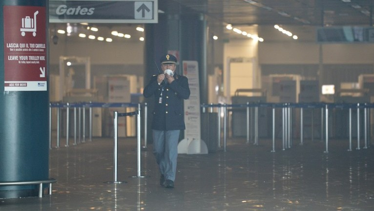 An officer wears a mask as he walks in Terminal 3 at Rome's Fiumicino international airport after a fire broke out overnight on May 7, 2015. (Photo credit: Tiziana Fabi/AFP)