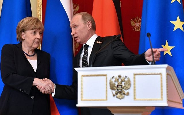 Russian President Vladimir Putin (R) shows the way to German Chancellor Angela Merkel as they leave a hall after a joint press conference at the Kremlin in Moscow on May 10, 2015. (photo credit: AFP PHOTO / KIRILL KUDRYAVTSEV)
