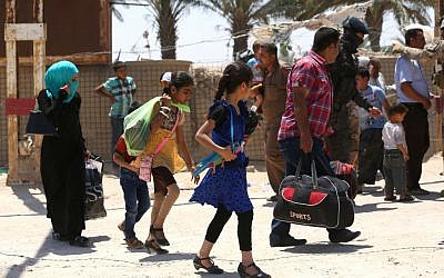 In this Saturday, May 16, 2015 photo, Iraqis fleeing from their hometown of Ramadi, Iraq, walk on a street near the Bzebiz bridge, 65 kilometers (40 miles) west of Baghdad.  (AP Photo/Hadi Mizban)