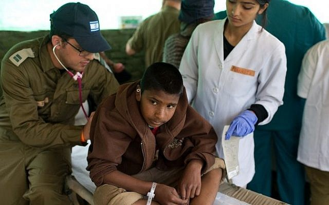 A Nepalese boy is treated by an Israeli army medic at the Israeli field hospital in Kathmandu on April 30, 2015. (AFP/ MENAHEM KAHANA)