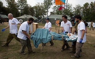 An Israeli army medic team carry Krishna Khadka, who was pulled out alive from a collapsed building, to a more thorough medical check at the Israeli field hospital in Kathmandu on May 1 2015. (photo credit: AFP/MENAHEM KAHANA)