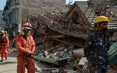 Rescue team officials arrive to search for survivors at a collapsed house in Kathmandu May 12, 2015, after an earthquake struck. (photo credit: AFP/PRAKASH MATHEMA)