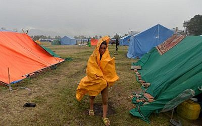 A Nepalese residents walks during a downpour at a relief camp for earthquake survivors in Kathmandu on May 23, 2015. (AFP/ISHARA S. KODIKARA)