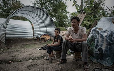 Earthquake survivor Navaraj Bista (R) and his son sit in front of their new shelter in the outskirts of Kathmandu following April 25's devastating 7.8 magnitude earthquake. May 8, 2015 (AFP/Philippe Lopez)